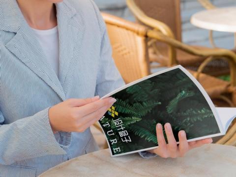 商务女士正在翻阅杂志的封面显示样机PSD图片模板