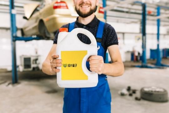4S店汽车维修工人拿着一桶机油psd样机图片模板素材